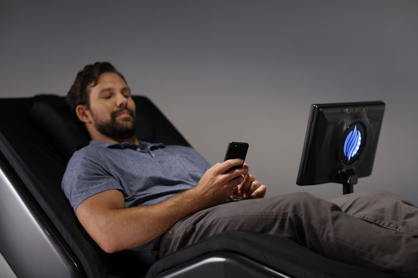 Man relaxing and working on his phone while using a HydroMassage Lounge 440X