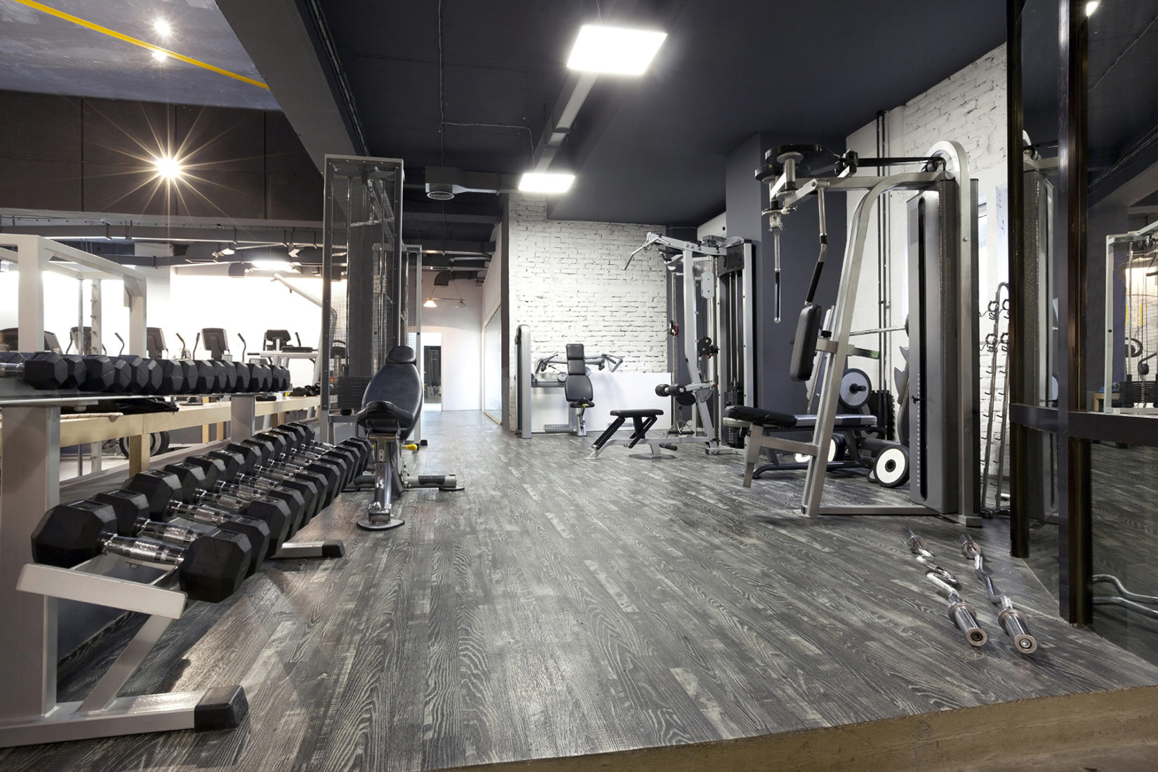 gym with racks of weights and machines with modern decor and design