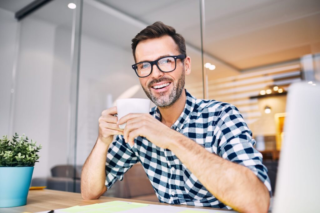 Man sitting at desk smiling and holding a cup of coffee, thinking about relaxing at home with a home massager