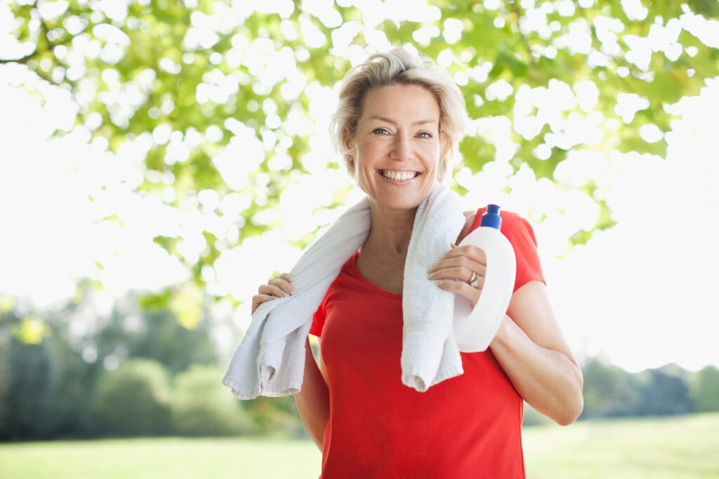 Mature woman standing outside in workout gear with a water bottle and towel, getting muscle soreness relief massage for pain