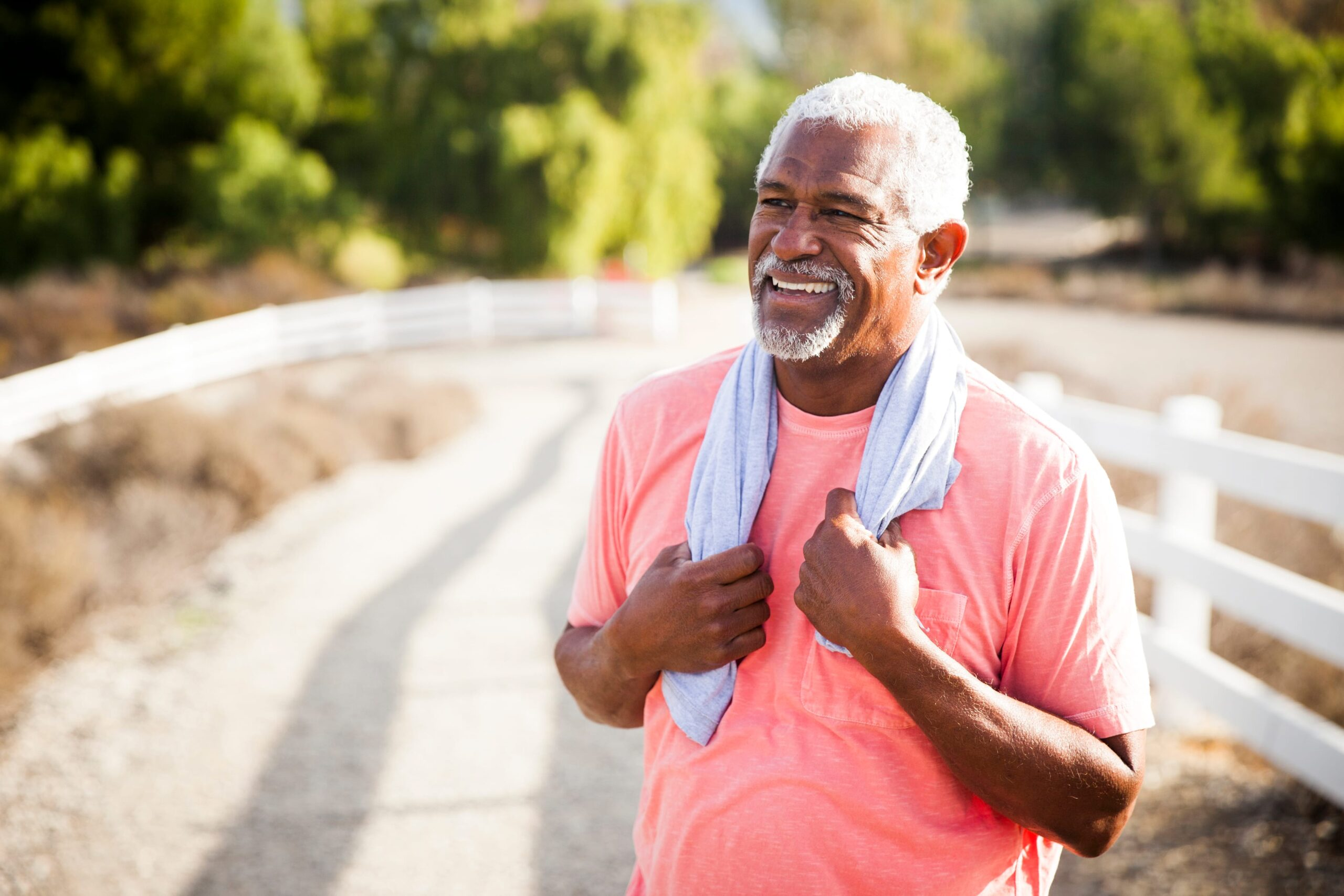 Older man standing outside with a towel after a workout, getting muscle pain relief for back pain